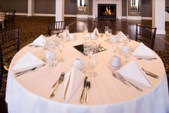 Banquet-room-with-white-place-settings-tables-with-fireplace-in-background