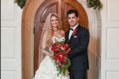 Bride-and-groom-smiling-in-front-of-wooden-door
