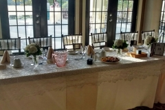 Long-wedding-table-with-glass-doors-behind