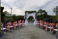 Wedding-arch-with-chairs-along-the-aisle
