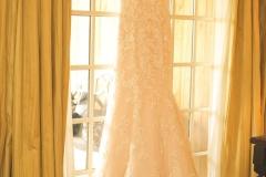 Wedding-dress-on-hanger-above-window