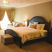 hotel suite bedroom with king bed, window, curtains, and ottoman