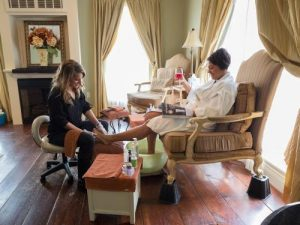 woman receiving a pedicure by a spa staff member with a drink in hand
