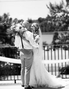 Black and white photo of bride and groom holding eachother
