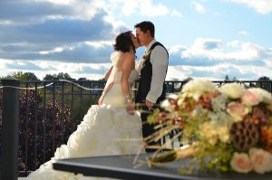 bride and groom kissing on the balcony