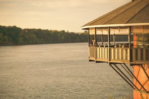bride and groom kissing on the pavillion with water view