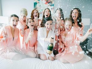 a group of women in peach robes celebrating with champagne