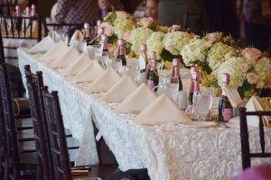 table setting with pink champagne bottles and napkins