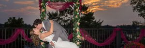 bride and groom kissing on the terrace at sunset