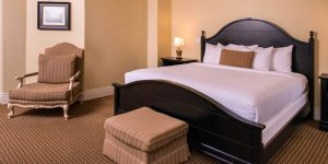 king size bed with white bedding next to ottoman and arm chair