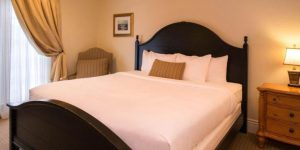 king bed with dark wooden headboard